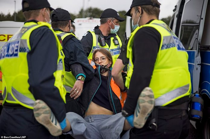 A protesterfrom the group Insulate Britain is arrested by police after being removed from the M25