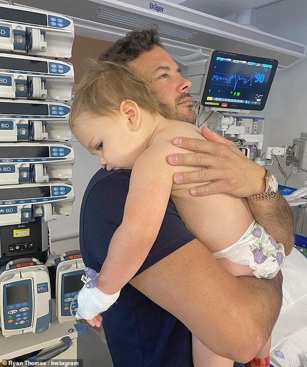 Fear: Lucy's son Roman, 18 months, was taken to intensive care and put on a ventilator after finding him 'blue in his cot' (Lucy's partner Ryan Thomas, pictured in hospital with Roman )