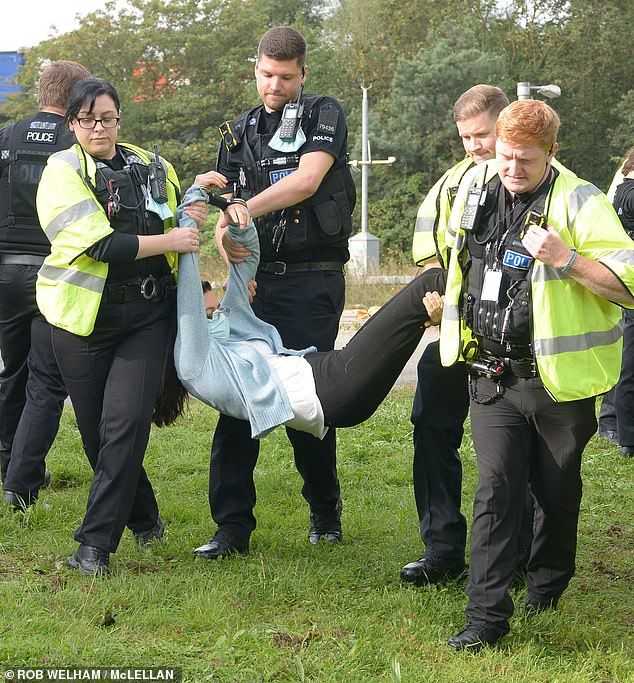 Police officers arrest an Insulate Britain protester who was blocking the M25