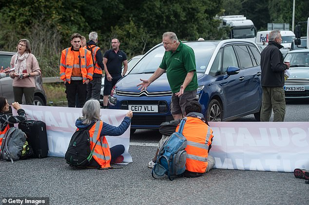 Angry motorists argue and jostle with activists as protesters from the Insulate Britain pressure group block a roundabout near Stansted Airport