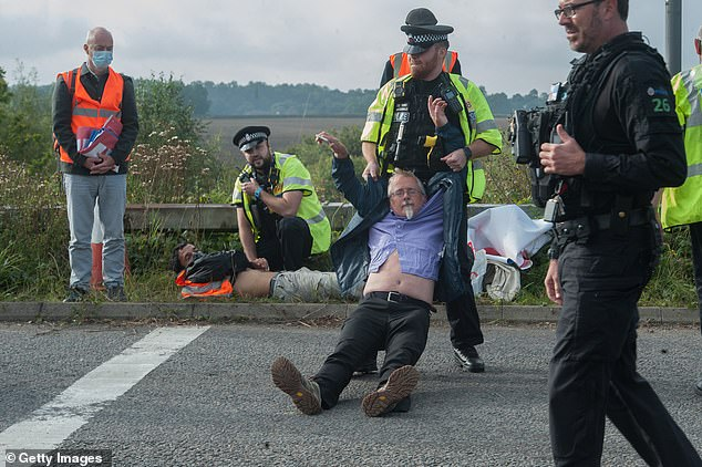 Police arrest activists as protesters from the Insulate Britain pressure group block a roundabout near Stansted Airport
