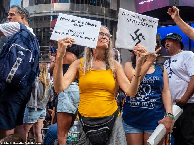Anti-vaccine mandate protesters gathered in Times Square to protest New York's Covid-19 vaccine mandate - and one woman likened the rule to hardships suffered by Jews in Nazi Germany