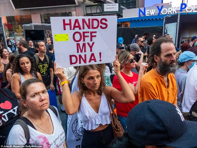 Hundreds of people lined the city streets holding American flags while one woman's sign read: 'Hands off my DNA!'