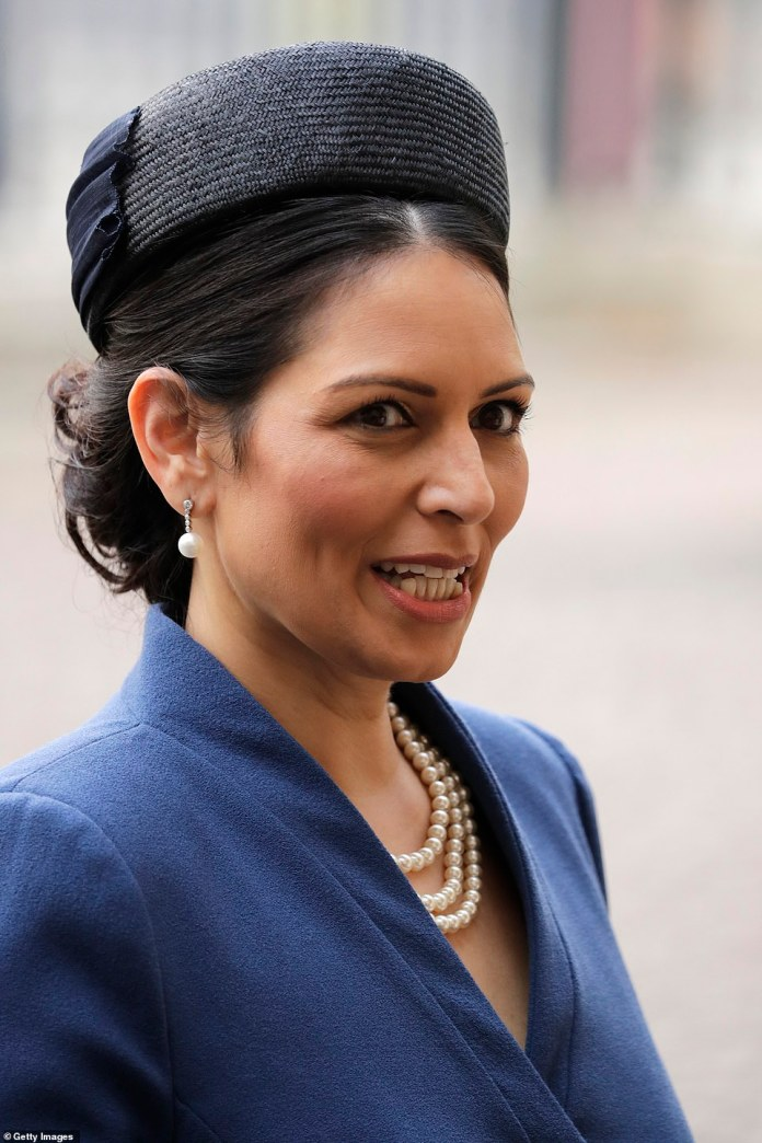 Ms Patel, 49, wore a three-tiered pearl necklace and matching pearl drop earrings, her hair neatly pinned under a military-style cap.