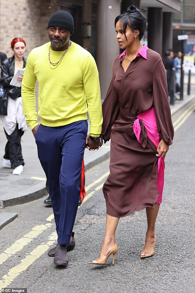 Chic:His model wife Sabrina cut a chic figure in a brown and hot pink midi dress, which featured a blouse-style collar and twist detail at the skirt