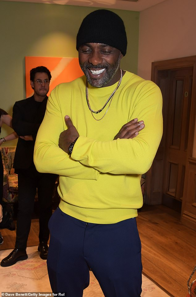 Age-defying:Idris Elba showcased his age-defying good looks as he modelled a canary yellow muscle-fit jumper as he was pictured for the London Fashion Week function