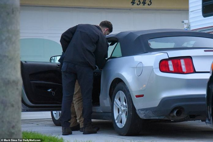 Two cops were seen searching a car which has been parked on the driveway of the home