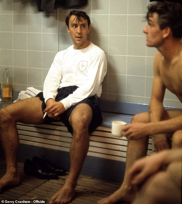 Jimmy Greaves smokes a cigarette as he talks with Ron Henry in the Spurs changing room