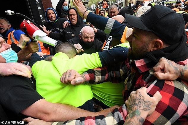 CFMEU representatives clash with protestors at the entrance of the office on Monday