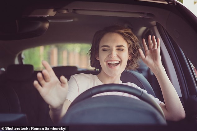 One study warns that playing singalong hits while behind the wheel can leave you 'mentally overloaded' and at risk of errors.  Or, as Rihanna might say: 'Shut up and drive!'  Pictured: A young woman sings to music in her car – and puts herself at risk (stock image)