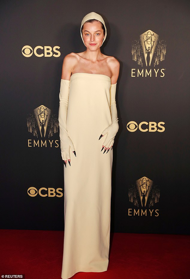 The Crown's Emma Corinne was ridiculed by social media users for her quirky Miu Miu Emmy outfit in a flesh-colored strapless gown, matching hooded hat and opera gloves.