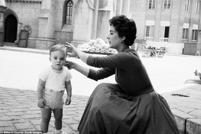 Taylor leads her baby son's locks in images, shot in color and black and white in France in 1954