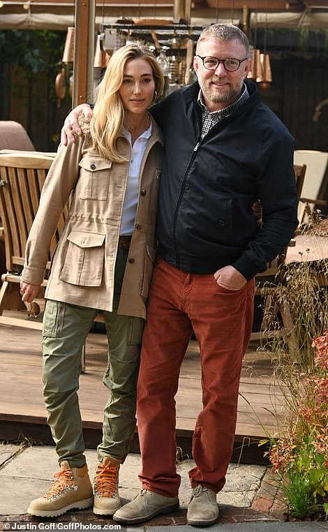 The director donned a pair of orange trousers, plaid shirt and casual coat while his wife was stylish in a white shirt and fashionable sunglasses