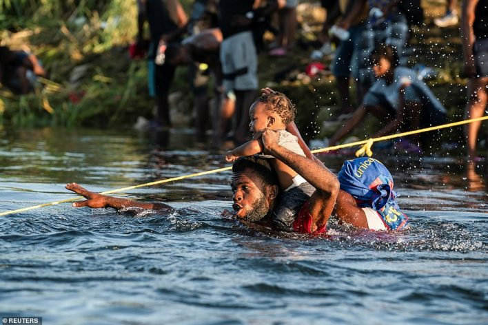 Two migrants with a child who are seeking asylum in the U.S. grabs onto a rope to guide themthrough while crossing the Rio Grande river into Mexico