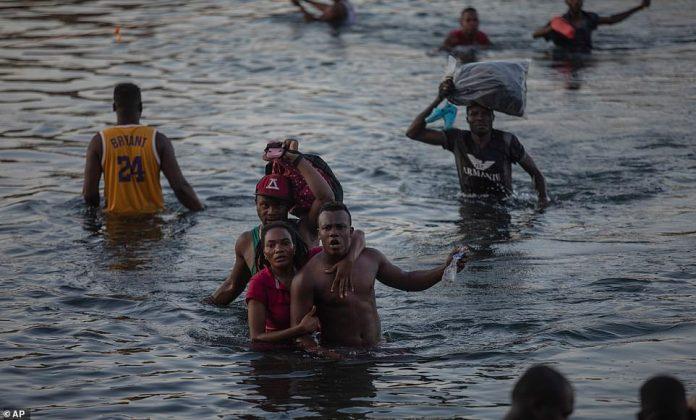 aitian migrants wade across the Rio Grande from Del Rio, Texas, tp Mexico on Sunday