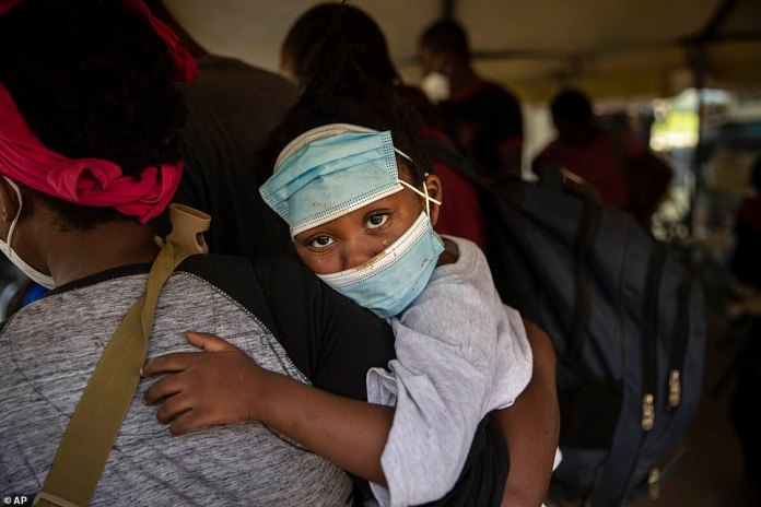 A little girl with teary eyes holds is carried by a woman who was deported from the U.S. border with Mexico at Toussaint Louverture International Airport in Port-au-Prince on Monday