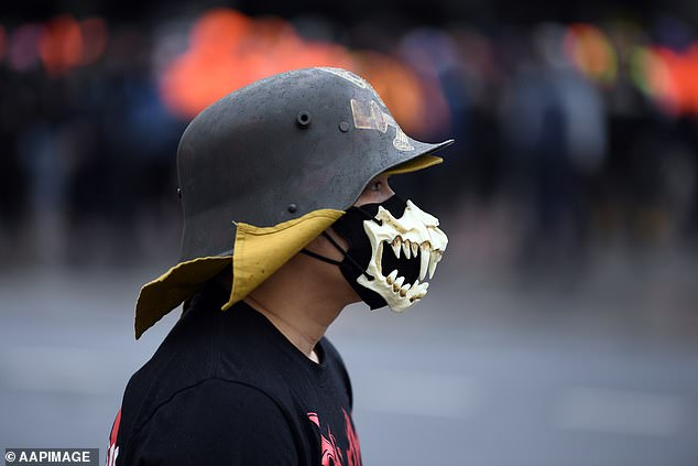 A protestor wearing a metal hat and a skeleton-style face mask is pictured at Tuesday's demonstration