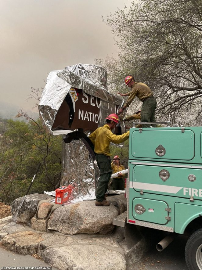 Firefighters wrap the historic Sequoia National Forest entrance sign with fire-proof blankets