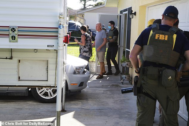 The image above shows FBI agents leading Chris and Roberta Laundrie out of their North Port, Florida home on Monday. The Laundries are the parents of Brian Laundrie, who has been missing and is considered a 'person of interest' in the disappearance of van-lifer Gabby Petito. The body believed to be that of Petito was found in Wyoming on Sunday