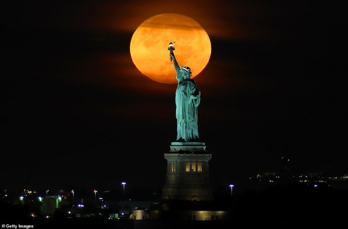 The Harvest Moon sets behind the Statue of Liberty before sunrise.  The September full moon was named the Harvest Moon in the 1700s, when farmers relied on the brightness of the moonlight to harvest late at night