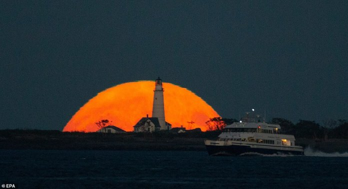 The Harvest Moon, also known as the Corn Moon, is seen behind the Boston Light as it rises in Boston, Massachusetts, US