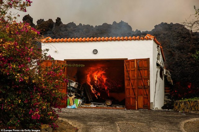 The garage of a home in the village of Los Llanos, La Palma, lights on fire as it is consumed by lava from the volcano