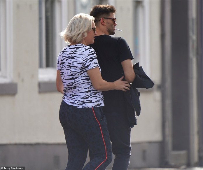 A gentle touch: Sarah clings to her pro mate as she arrives in training