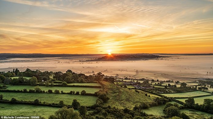 The 'sea' of Somerset is seen from Glastonbury Tor as a shroud of fog appears to flood the Levels at the break of dawn on Tuesday morning, the last day of summer