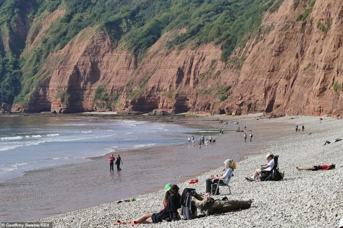 People soak up the last of the British summer on the Jacobs Ladder Beach, Sidmouth, Devon. Tomorrow sparks the official start of autumn