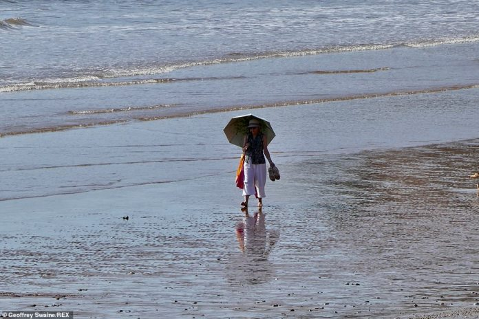 Another woman opts for the umbrella to block out the bright spells of sunshine experienced in Sidmouth, Devon, on Tuesday morning