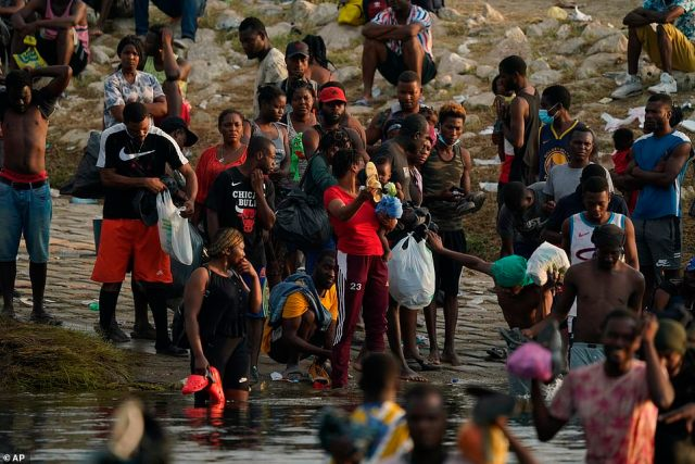 Mostly Haitian migrants stand on the U.S. side of the bank of the Rio Grande River as they prepare to wade from Del Rio, Texas on Tuesday to Ciudad Acuna, Mexico to avoid deportation back to their homeland