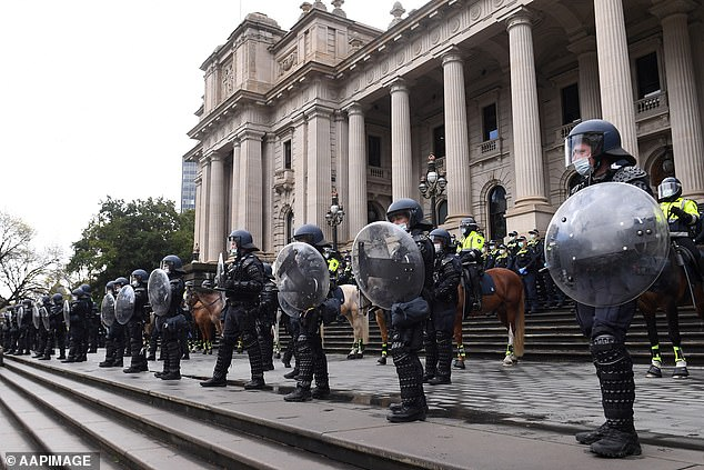 Riot police are seen outside the Victoria's Parliament House during Tuesday's protest