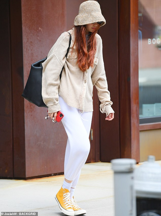 Legging it:The 26-year-old supermodel accented her look with a tan cardigan and shielded her face from the rays with a slouched hat