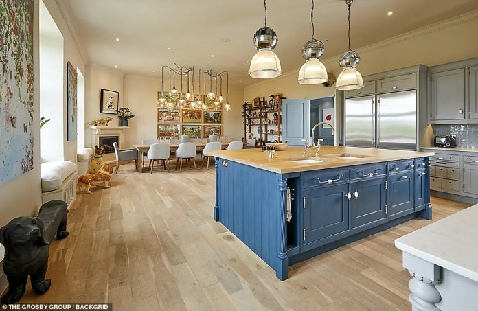 Quirky: The gourmet chef's kitchen is an impressive feature of the home with a stunning blue wooden island and a spacious dining space perfect for large gatherings.