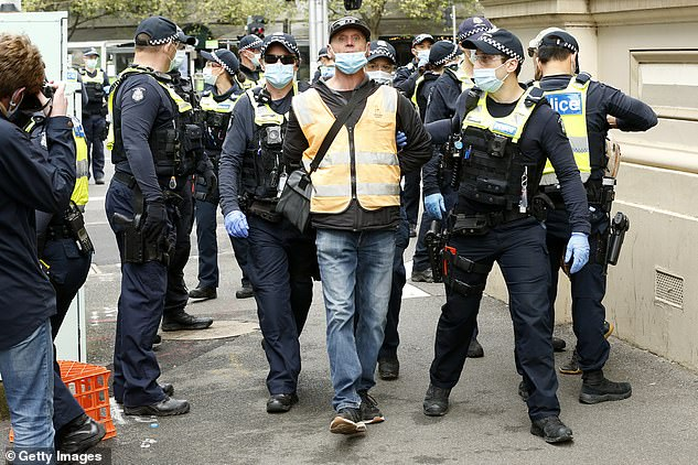 Members of Victorian Police detain a man at the corner of Elizabeth St and Victoria St near the CFMEU Building on Wednesday