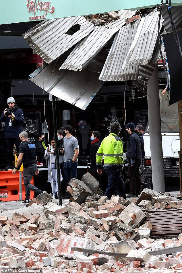 The earthquake caused significant damage to buildings in Melbourne. Onlookers are pictured gathering at the city's popular Chapel Street shopping centre on Wednesday morning