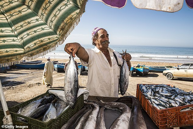 A fisherman shows off his catch on the beach inTaghazout. The baystarted life as a fishing village