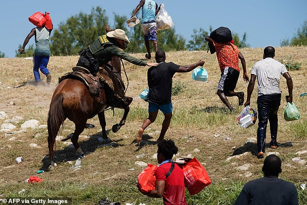 A United States Border Patrol agent on horseback tries to stop a Haitian migrant from entering an encampment on the banks of the Rio Grande