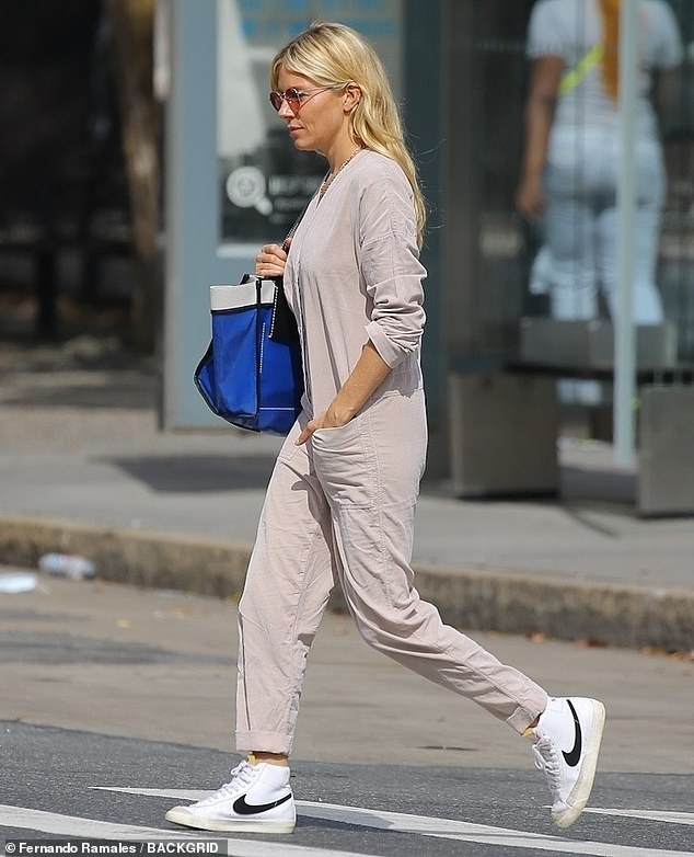 Out: The actress added a '70s touch to her look with red tinted round-frame sunglasses and sneakers and carried her essentials in an oversized blue leather tote bag