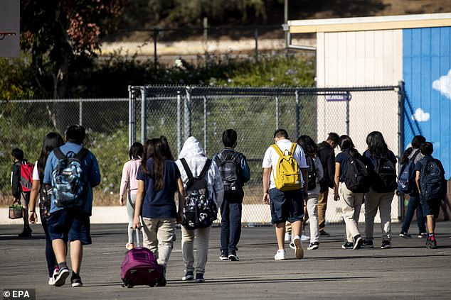 Of the more than 30,000 close contacts of COVID-19 patients, only 63 contracted the virus, which is equivalent to 0.2%.  Pictured: Students go to their classes at a middle school in El Sereno, East Los Angeles, September 10