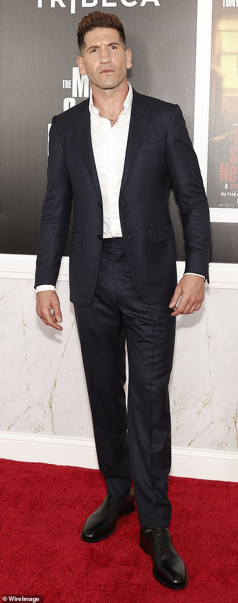 Suave: Jon Bernthal looked suave in a fitted suit and a bright white button-up shirt as he struck poses in front of The Many Saints Of Newark backdrop