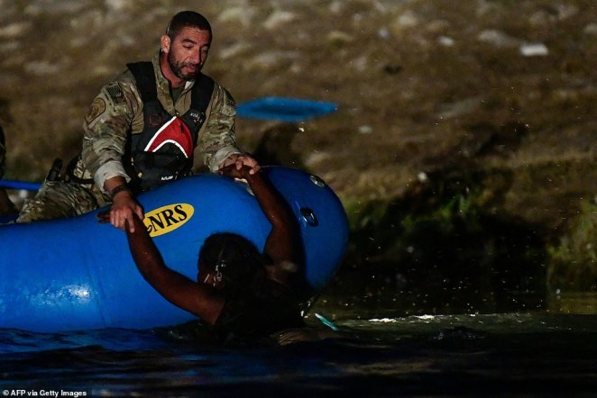 US Customs and Border Protection (CBP) agents on a boat rescue a Haitian migrant woman from the Rio Grande river at the Mex ico-US border near Ciudad Acuna, Coahuila state, Mexico on Thursday