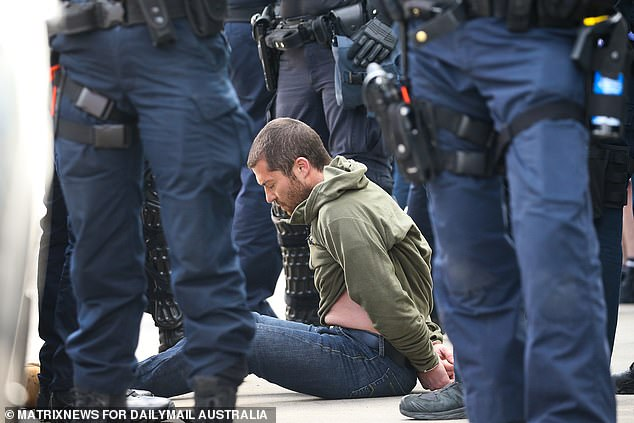 Pictured: Victoria Police arrest a man at Friday's protest in All Nations Park, Melbourne