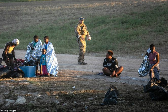 Border Patrol agents pass by Haitian families wrapped up for warmth after crossing the Rio Grande River to reach the U.S. from Mexico