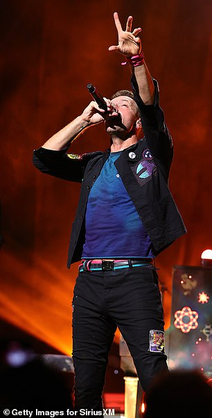 Chris donning a navy t-shirt and black pants with a stylish multicolored patch
