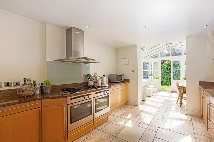 The kitchen at Amerden Bank has a tiled floor that leads through the conservatory that opens to a landscaped garden