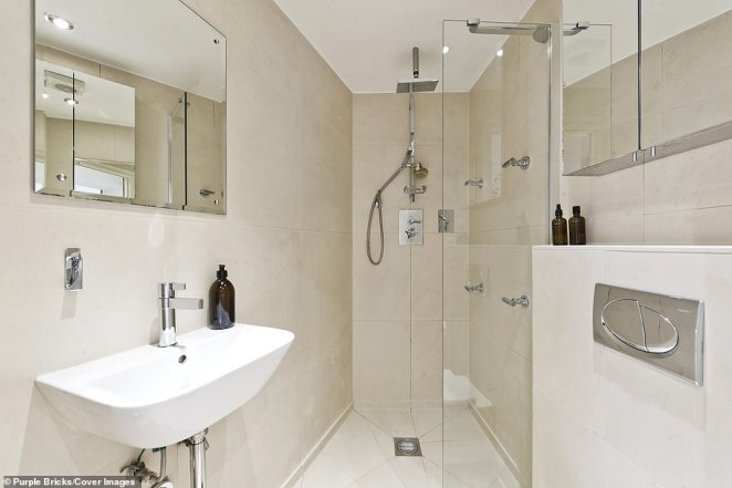 The bathroom boasts a walk-in shower, glass mirrored cabinets and stone-coloured panelling