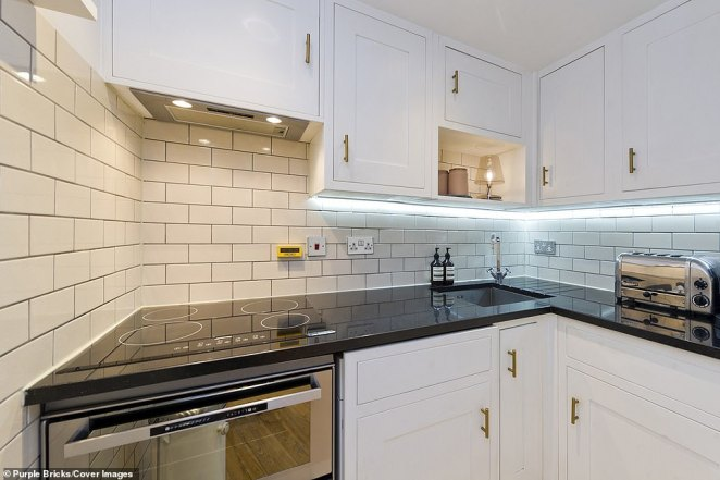 The sleek and compact kitchen features an electric hob and oven and white brick-like tiling