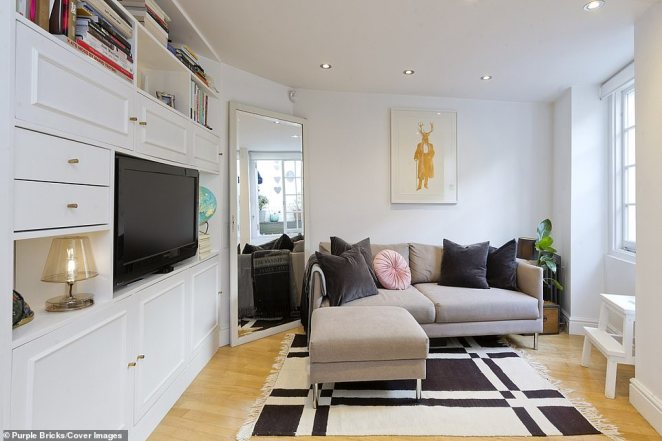 Large bay windows and an almost floor length mirror help create a spacious-feeling living room