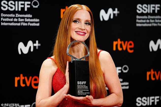 She's sizzling: Her fiery red hair hangs over her shoulders as she poses on the red carpet with her award